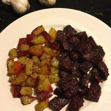 Herb Garlic Roasted Beets on white plate with 2 heads of garlic in the background