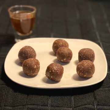 No-Bake-Coconut-Rum-Balls on a white plate with a shot glass of rum in the background