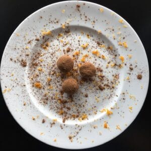 orange chocolate avocado truffles on a white plate with cocoa powder and orange zest sprinkled on truffles and plate