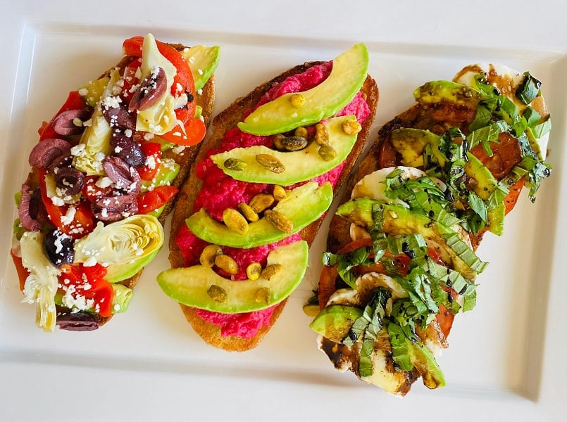 3 slices of avocado toast on bread with different toppings on each