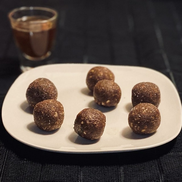 coconut rum balls on a plate with a shot of rum in background