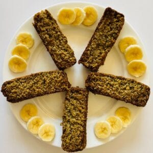 5 slices of banana bread on a plate with bananas