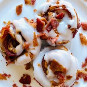 Bacon-Cinnamon-Rolls-on-plate-with-icing-and-bacon-topping