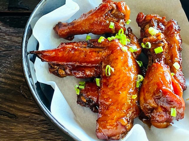Chicken wings on a plate covered in best chicken wing sauce