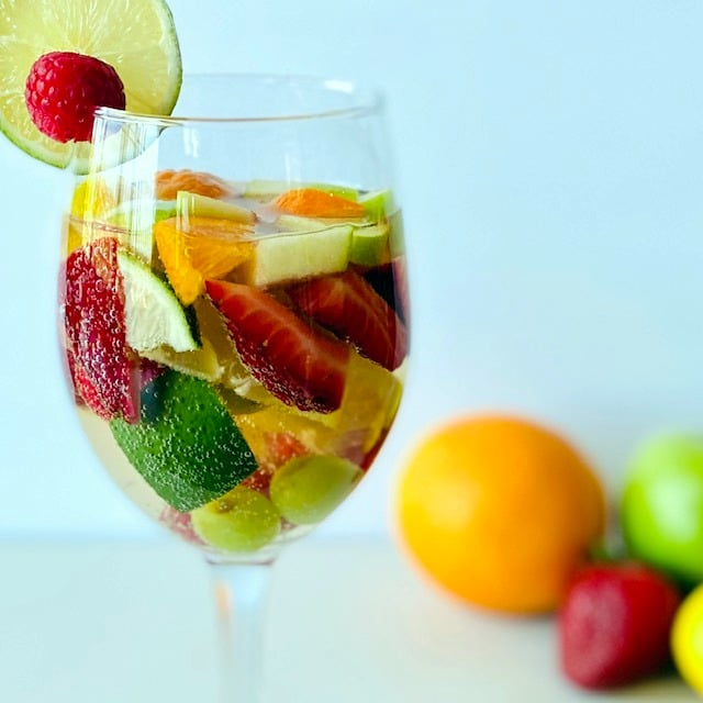 white-sangria-in-wine-glass-with-fruit-and-fruit-in-background