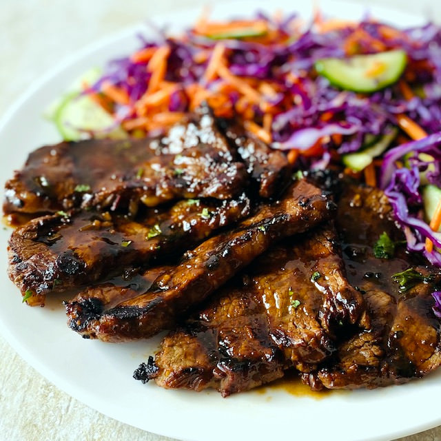 marinated-grilled-steak-on-plate-with-asian-slaw-on-side