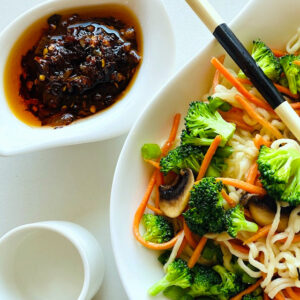 chili-crisp-in-dish-and-bowl-of-noodles-vegetables-and-chopsticks
