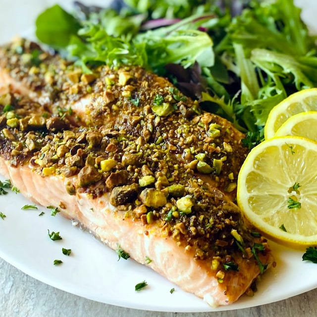 pistachio crusted salmon on a white plate with lemons and greens
