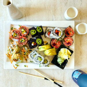 vegetable-sushi--different-kinds-on-plate-next to chopsticks-and-sake