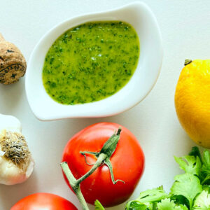 cilantro dressing in white cup surrounded by tomato lemon cilantro and garlic