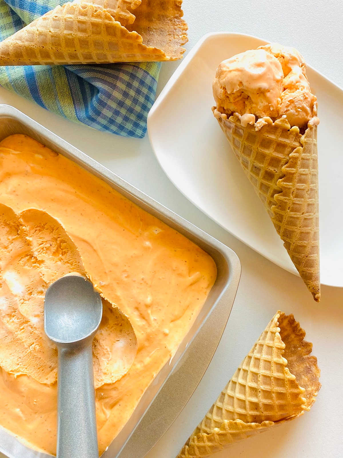 thai tea ice cream in metal tin next to ice cream cones -