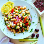 Mediterranean chickpea salad in a white bowl next to a dish of kalamata dressing