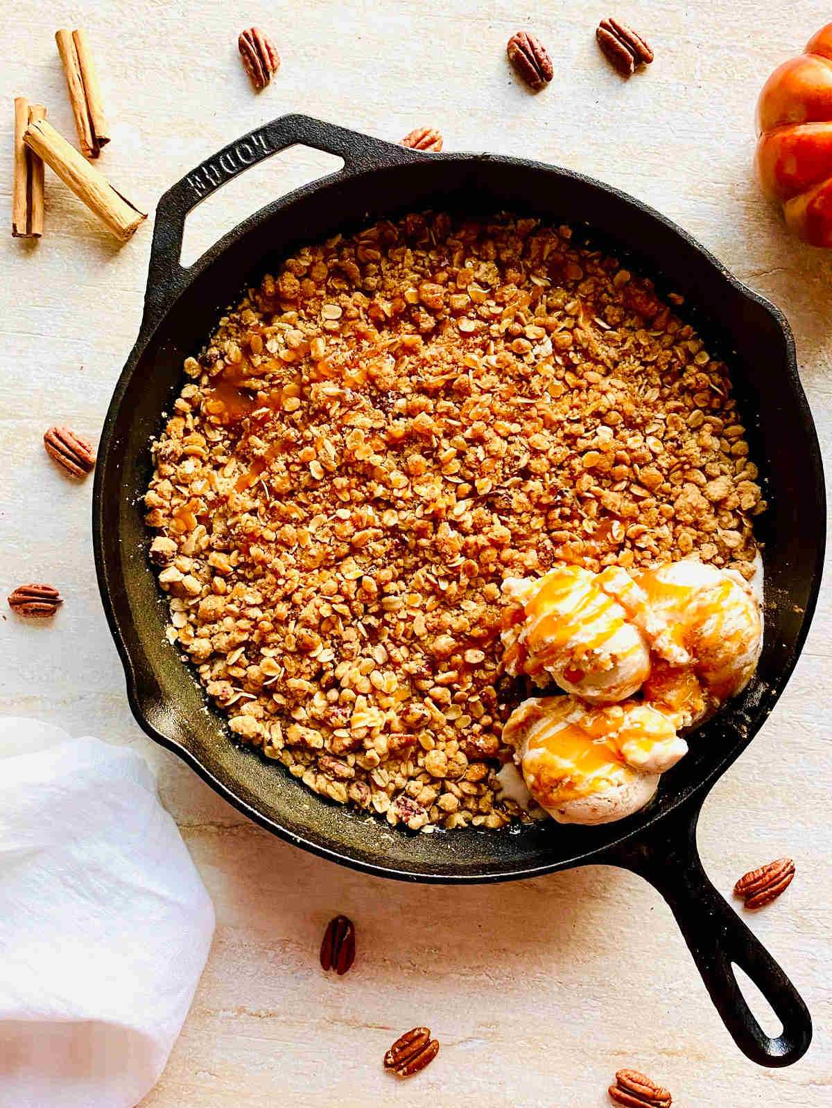 cast iron skillet apple crisp with ice cream next to pecans and a pumpkin