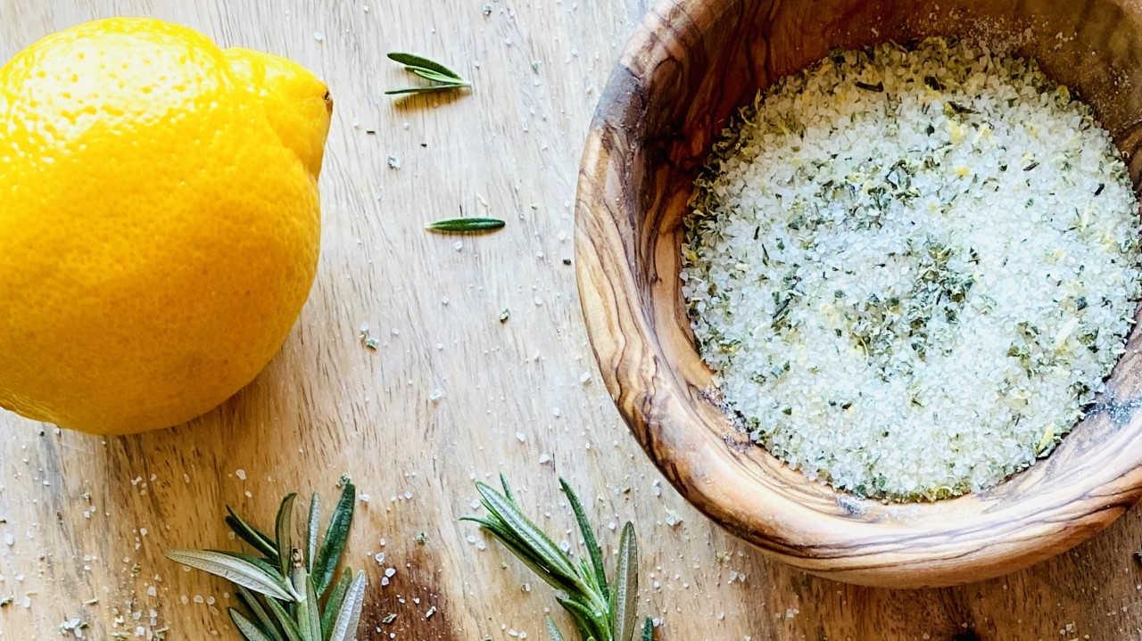 Rosemary salt in bowl next to lemon and rosemary