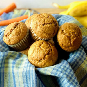 banana carrot muffins in basket with carrot and banana in background