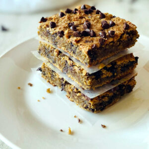 vegan blondies in a stack separated by parchment paper on a white plate