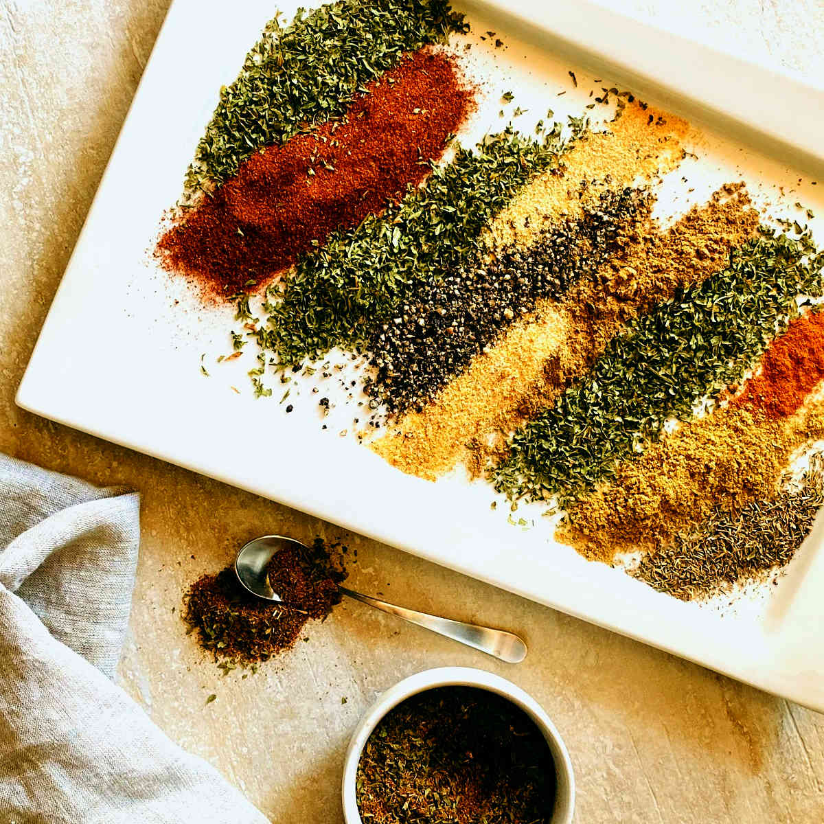 Tempero baiano brazilian spices layered next to each other on a white plate next to a dish of mixed seasoning and a spoonful