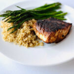 blackened cod on a plate next to quinoa and roasted asparagus
