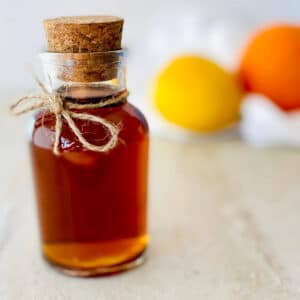 demerara syrup in bottle with lemon and orange in background