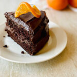 orange chocolate cake on a white plate garnished with a candied orange slice on top
