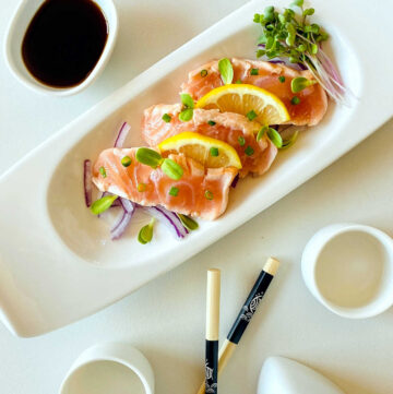salmon tataki on plate garnished with lemon onion and sprouts next to chopsticks and ponzu