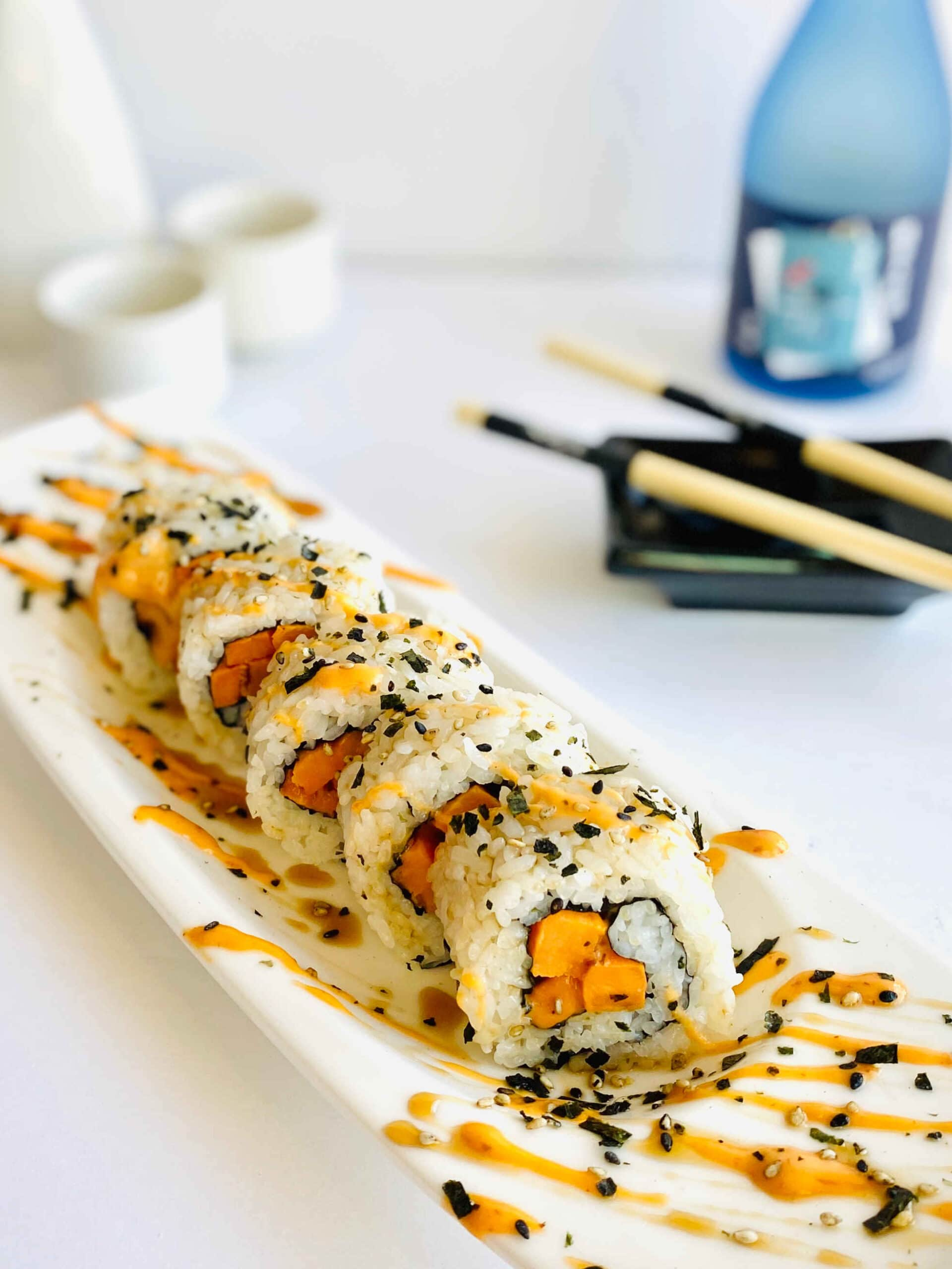 sweet potato roll sushi on plate with sake bottle and chopsticks in background