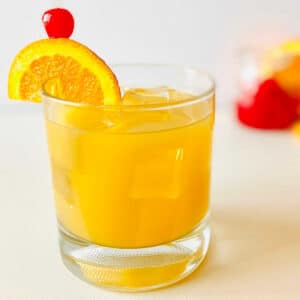 whiskey sour mocktail in rocks glass garnished with orange and cherry