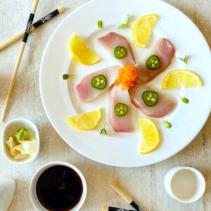 yellowtail sashimi slices on white plate topped with jalapeno slices and surrounded by lemon slices, soy sauce and chopsticks