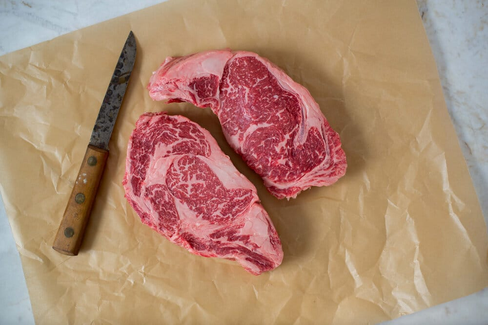 two american wagyu steaks on butcher paper next to a knife