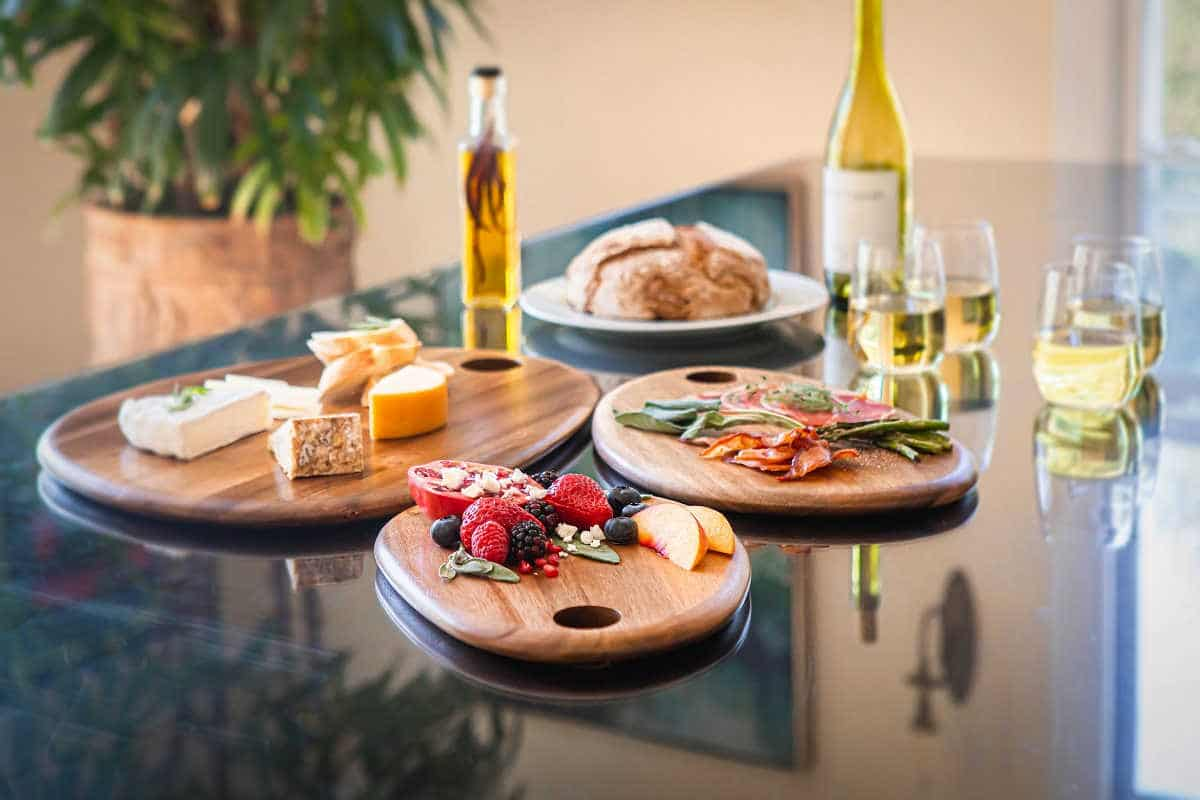 charcuterie boards of different sizes with glasses of wine, meats and cheeses