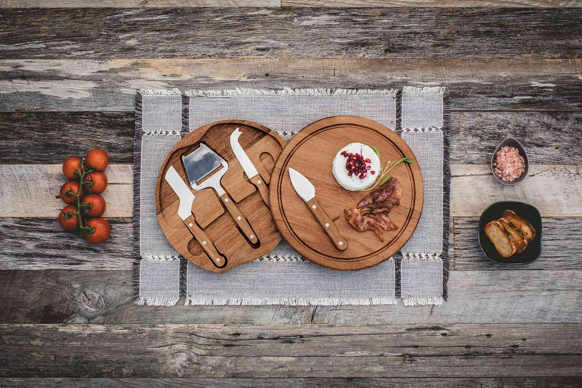 cheese board with cheese cutting utensils surrounded by cheese and meat