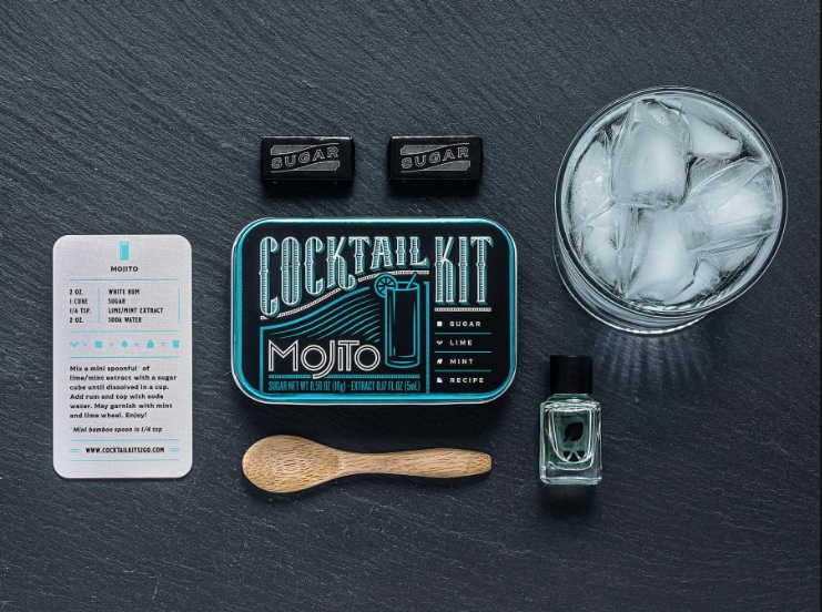mojito cocktail kit tin next to glass of ice, spoon and recipe card