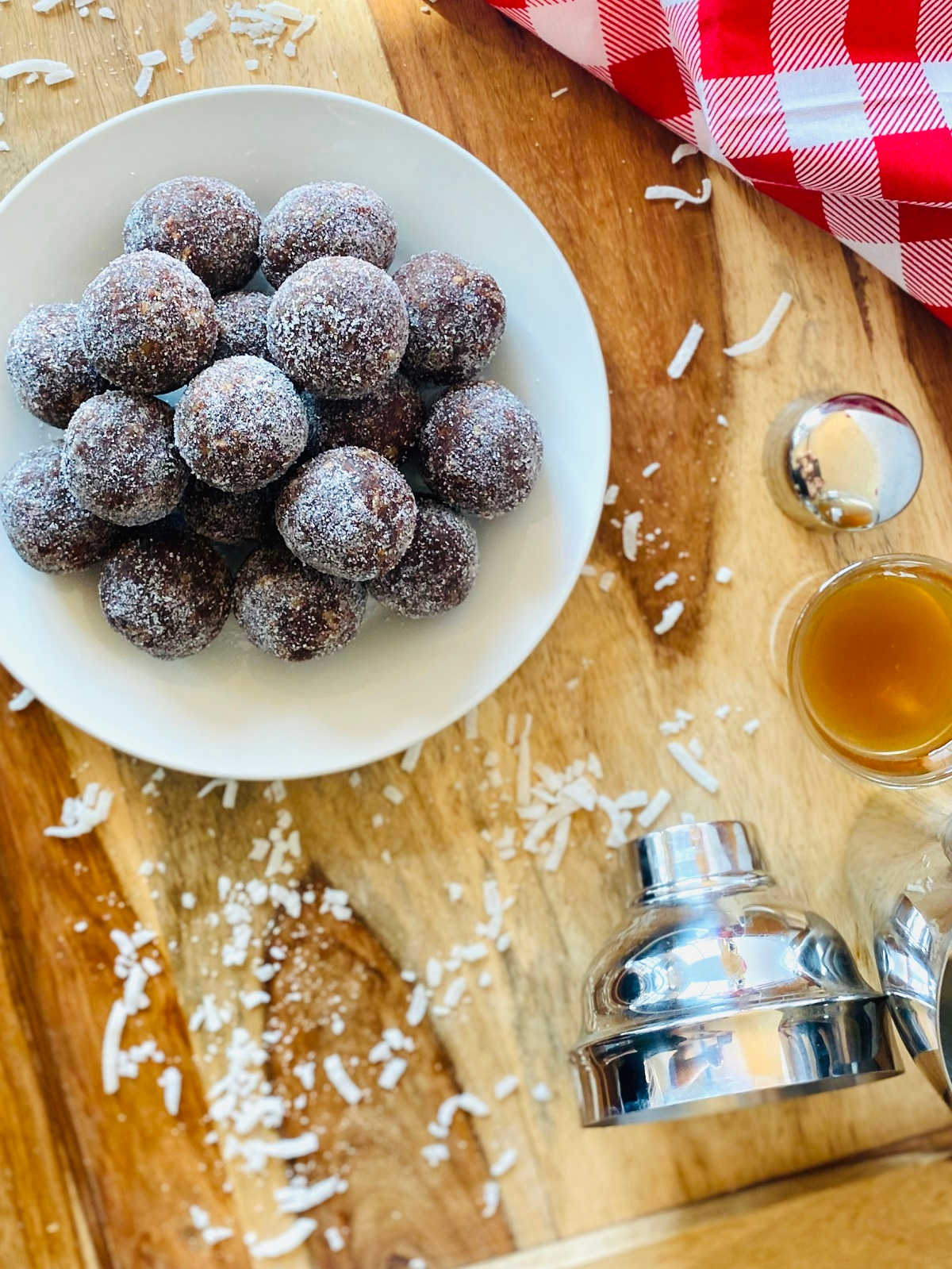 coconut rum balls on a plate next to rum shot, martini shaker and red linen