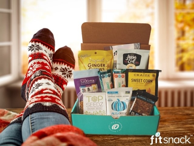 fitsnack gift box on table with feet relaxing in holiday socks next to the box