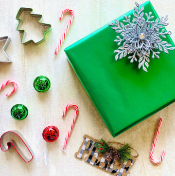 holiday present wrapped with a star shaped bow surrounded by candy canes, cookie cutters and bells