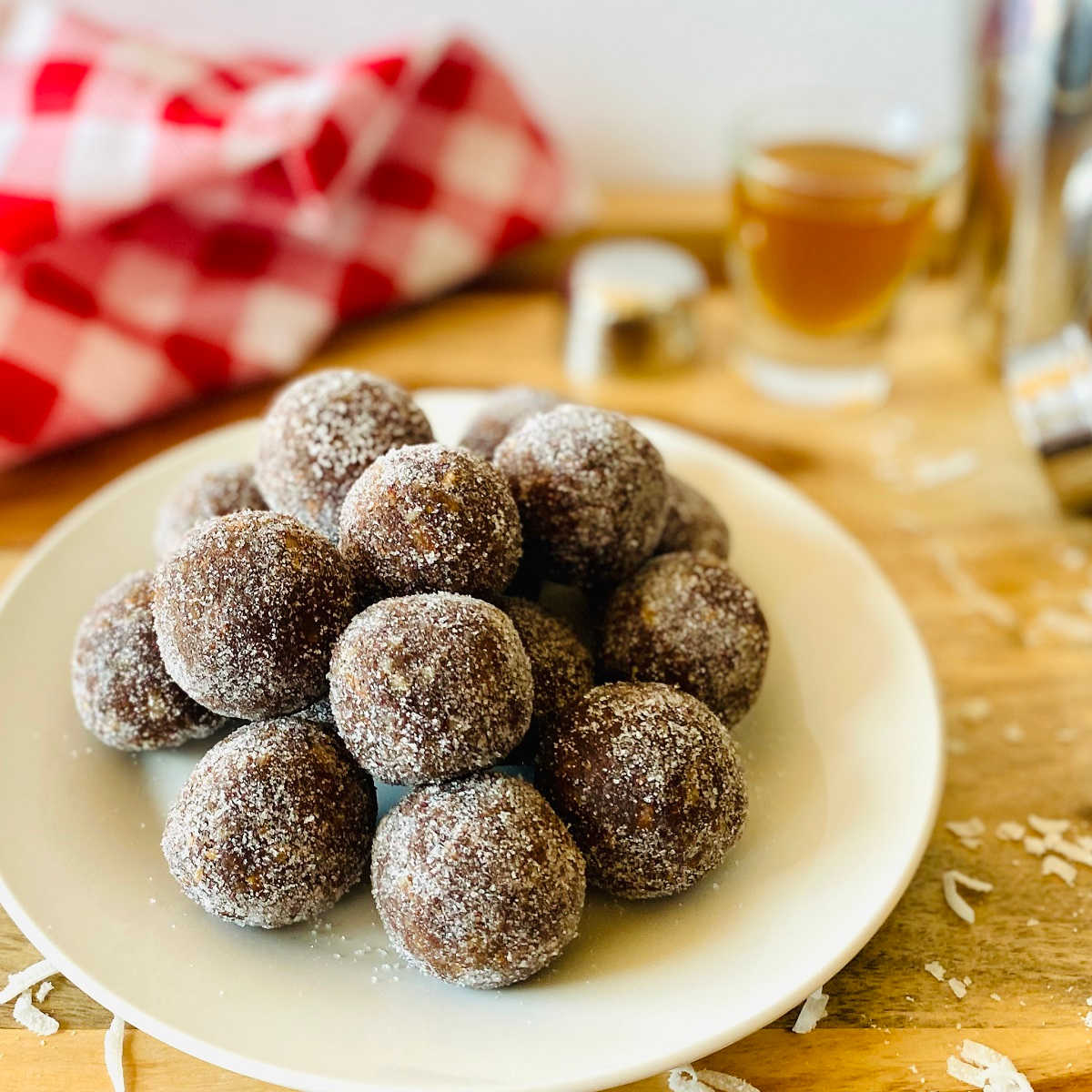 coconut rum balls on a plate next with red linen and shot of rum in the background
