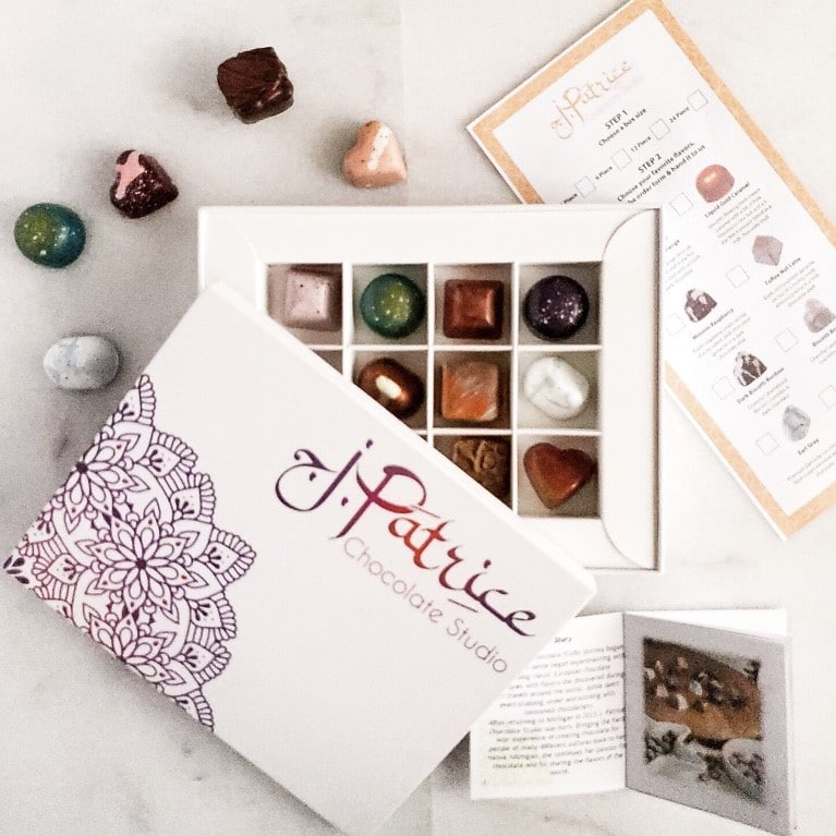 box of gourmet chocolates in a box next to chocolates and a card explaining flavors
