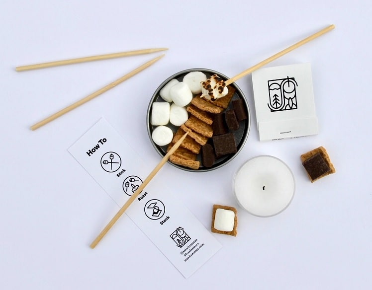 small smores kit with mini graham crackers, chocolate and marshmallow sitting next to candle and sticks to roast