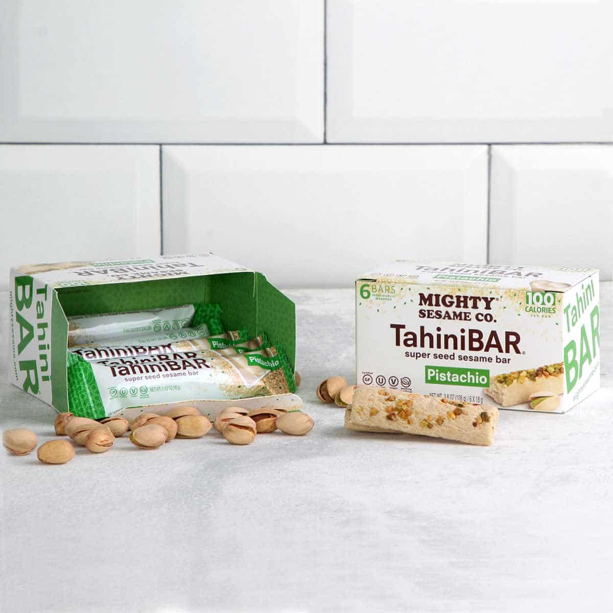 tahini bar box sitting next to tahini bars and pistachios