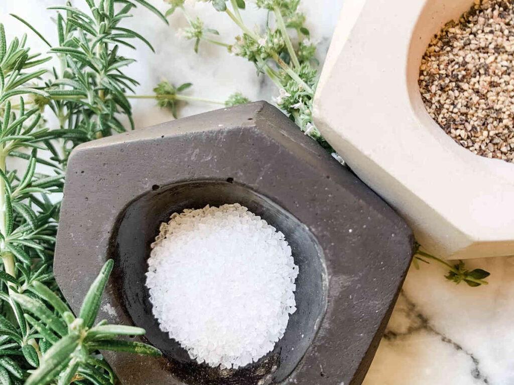 two concrete handmade salt cellars holding salt and pepper