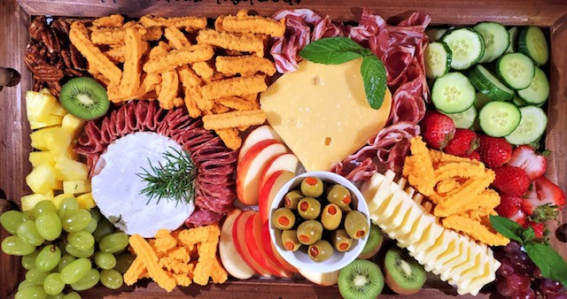 charcuterie board with meats, cheeses, olives and grapes