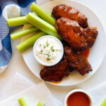 air fryer chicken wings on a plate next to celery and blue cheese