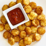 air fryer tater tots on white plate with dish of ketchup