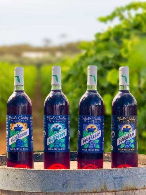 four bottles of blueberry wine