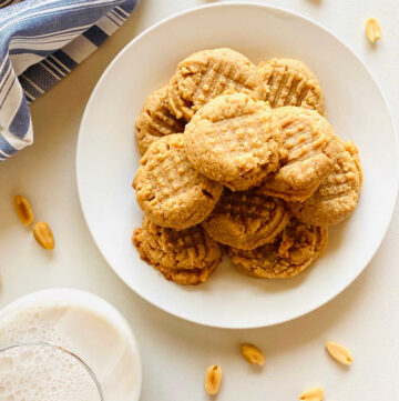 almond flour peanut butter cookies on plate next to glass of milk