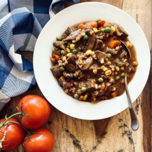 instant pot vegetable beef soup in white bowl with spoon next to napkin, tomatoes and herbs