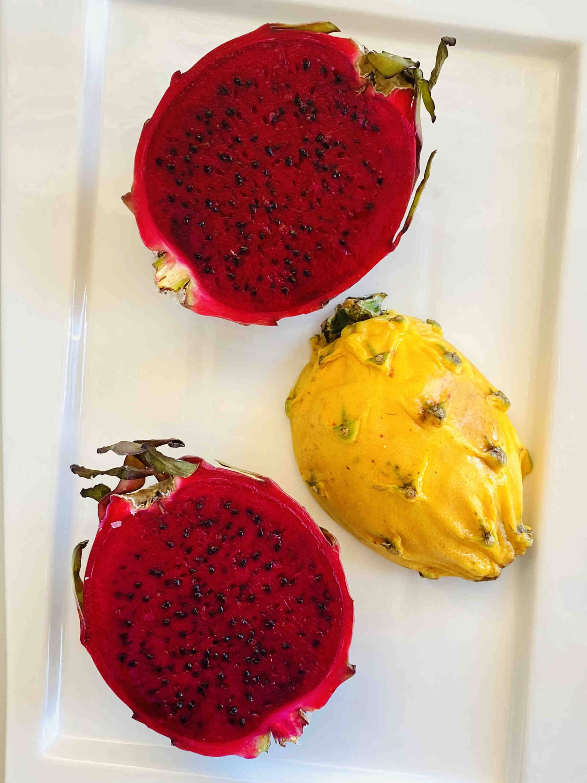 red dragon fruit and yellow dragon fruit sliced in half on a white rectangular plate