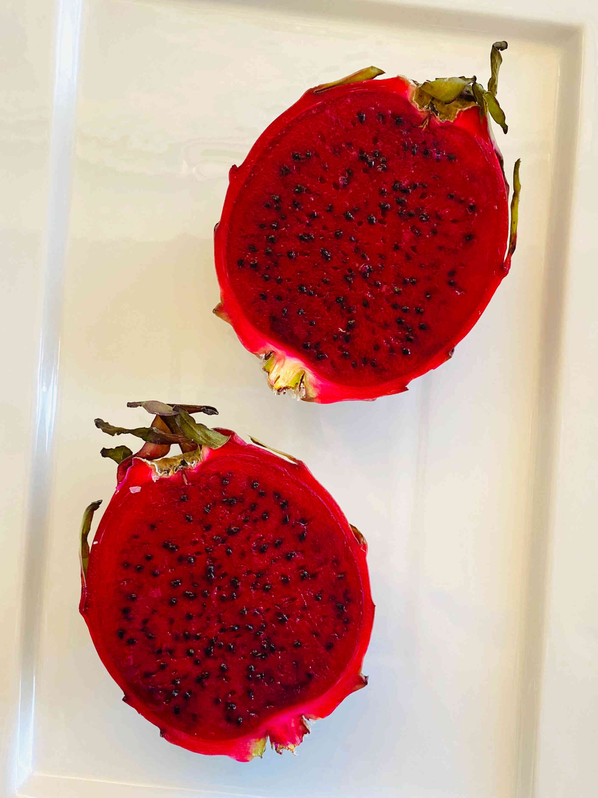 red dragon fruit sliced in half on a white rectangular plate
