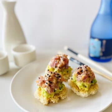 spicy tuna crispy rice on plate next to chopsticks, sake and sake carafe and glasses