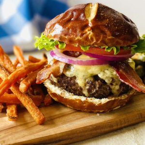american wagyu burger on cutting board next to sweet potato fries